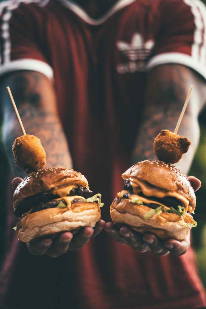 person holding two hamburgers