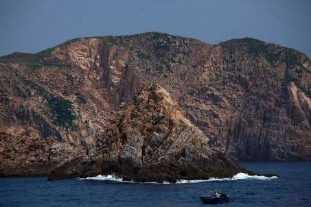 People fish in a boat off Ninepin Group, also known as Kwo Chau Islands, where large hexagonal columns of volcanic rock are exposed, southeast of Hong Kong, August 30, 2012. An ancient supervolcano that last erupted 140 million years ago, considered as one of the oldest supervolcanos, has been discovered in the southeastern part of Hong Kong, the Hong Kong Geological Survey under the government's Civil Engineering and Development Department said on Thursday. It added that this is the first discovery of an ancient supervolcano in southeastern China. REUTERS/Bobby Yip (CHINA - Tags: ENVIRONMENT SOCIETY)