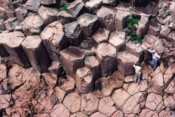 People stand on large hexagonal columns of volcanic rock on Ninepin Group, also known as Kwo Chau Islands, southeast of Hong Kong in this handout photo released August 30, 2012. An ancient supervolcano that last erupted 140 million years ago, considered as one of the oldest supervolcanos, has been discovered in the southeastern part of Hong Kong, the Hong Kong Geological Survey under the government's Civil Engineering and Development Department said on Thursday. It added that this is the first discovery of an ancient supervolcano in southeastern China. REUTERS/Hong Kong Government's Civil Engineering and Development Department/Handout (CHINA - Tags: ENVIRONMENT SOCIETY TPX IMAGES OF THE DAY) NO SALES. NO ARCHIVES. FOR EDITORIAL USE ONLY. NOT FOR SALE FOR MARKETING OR ADVERTISING CAMPAIGNS. THIS IMAGE HAS BEEN SUPPLIED BY A THIRD PARTY. IT IS DISTRIBUTED, EXACTLY AS RECEIVED BY REUTERS, AS A SERVICE TO CLIENTS