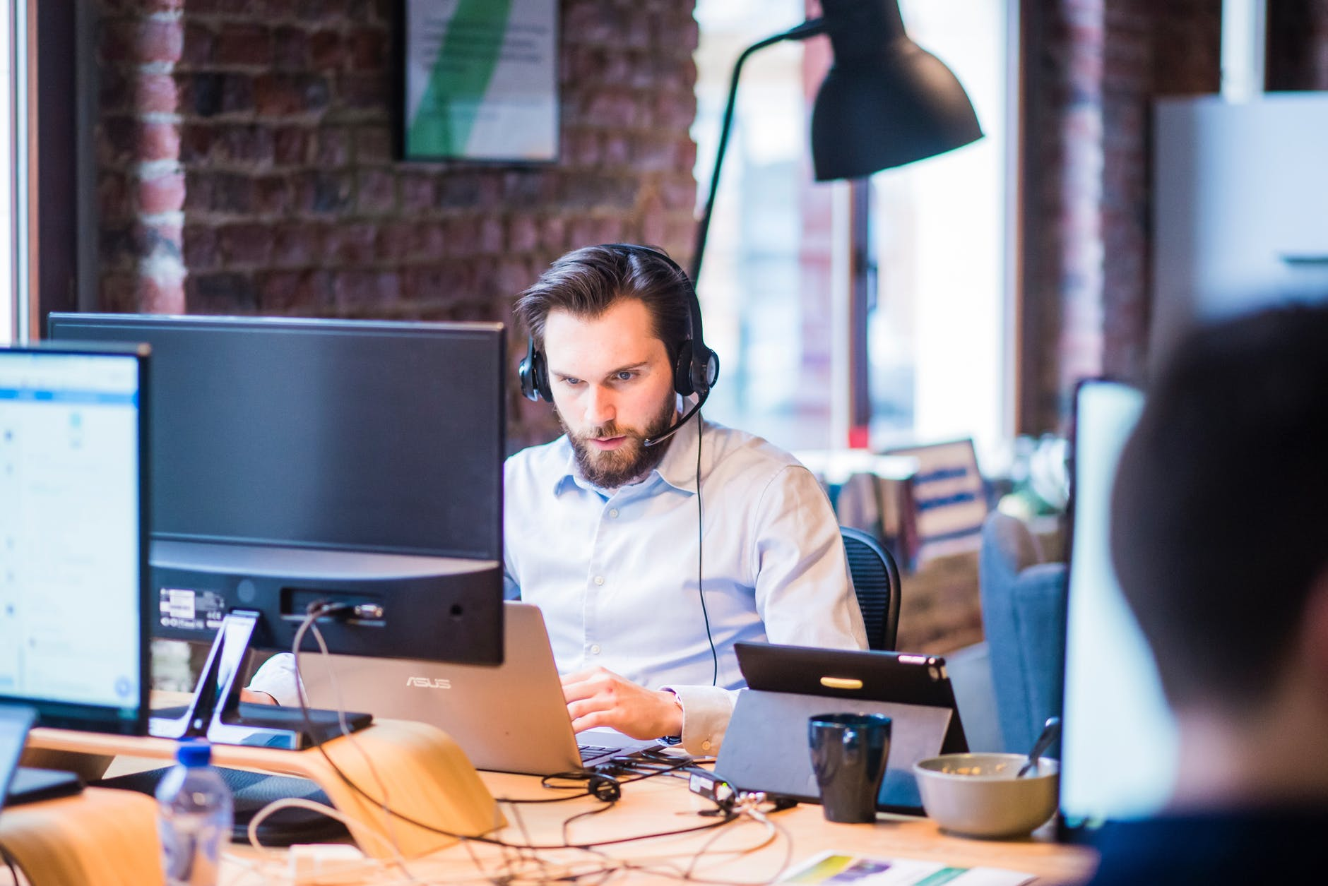 selective focus photo of man in official shirt sitting in office working on laptop