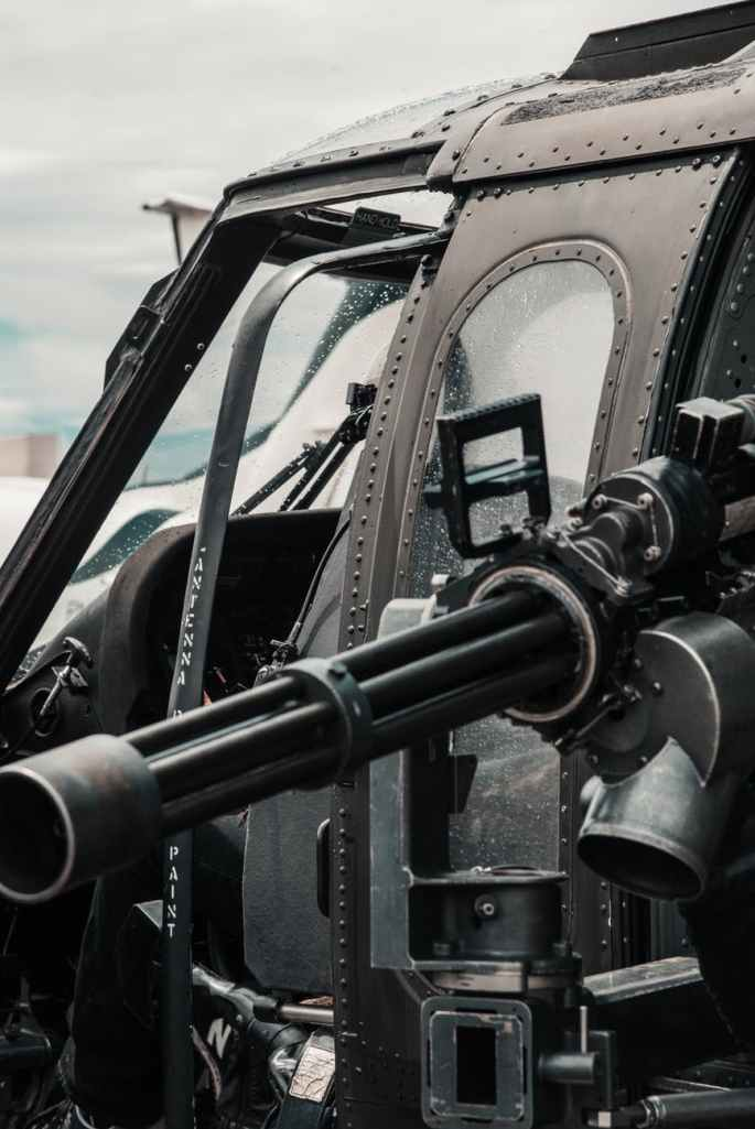 close up photo of black helicopter with black machine gun